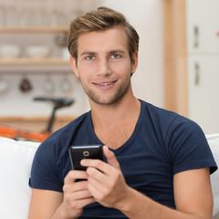 lächelnder mann mit handy in seiner wohnung
