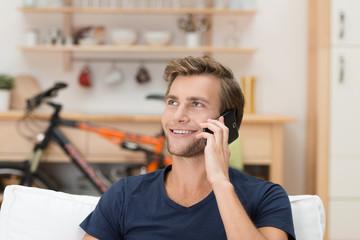 lächelnder mann telefoniert zuhause mit handy