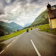 Fototapete - Biker race across mountainous village