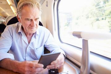 Senior Man Reading E Book On Train Journey