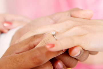 Close up of young male holding woman hand