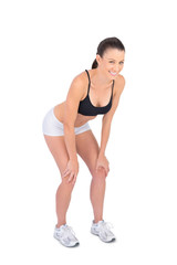 Cheerful fit model in sportswear posing hands on lap