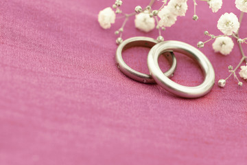 Wedding rings on soft pink background with copy space