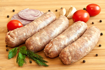 Uncooked sausages with vegetables on the chopping board