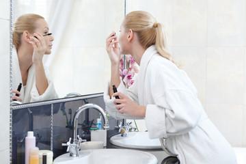 Young girl mascaras her eyelashes in bathroom