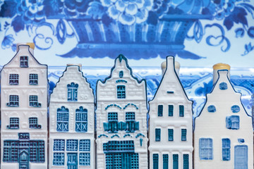 Dutch Delft blue souvenir houses in front of an old plate