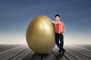 Businessman standing by a huge golden egg