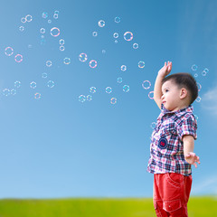Baby little asian boy standing against blue sky with soap bubble