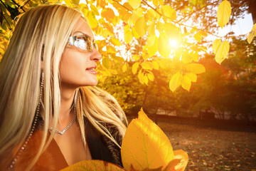 Wall Mural - Autumn woman with yellow fall leaves in park.