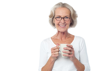 Smiling bespectacled old lady drinking coffee