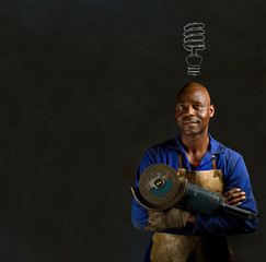 African industrial worker with engery saver on blackboard