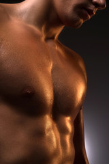 Muscular man. Close-up of muscular man standing isolated on whit