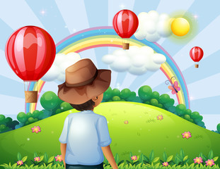 A boy at the hilltop with flying balloons and a rainbow