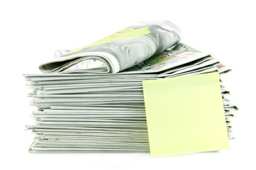 pile of newspaper with yellow stick note isolated on white backg