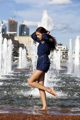 Young sexy woman in a city fountain