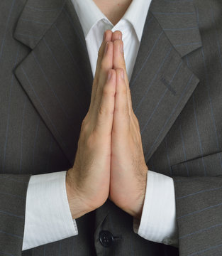 praying executive asking to do well in the shareholders' meeting
