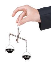 Hand keeps metal weighting imbalanced scales