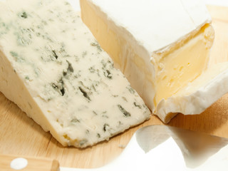 Brie and dor blue cheese on wooden desk with knife