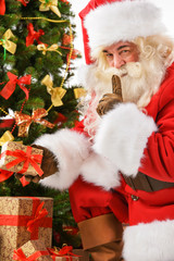 Santa Claus bringing gifts and putting under Christmas tree