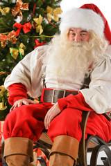 Santa Claus sitting in rocking chair near Christmas Tree