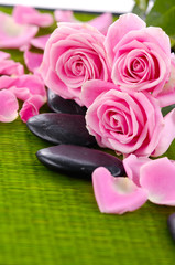 pink roses with stones on green mat