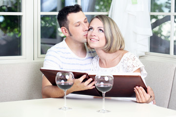 Beautiful young romantic  couple with photo, at home