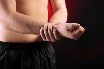 Young man with hand pain, on red background