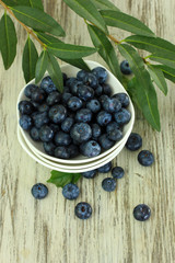 Blueberries in bowls on wooden table