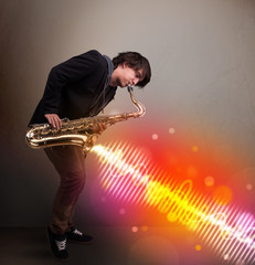 Young man playing on saxophone with colorful sound waves