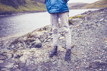 Close up on hillwalkers feet and legs by water