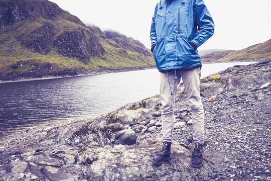Hillwalker standing by mountain lake