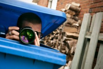 Paparazzi hiding in a blue garbage bin