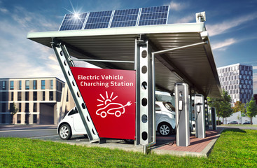 E-Cars on Electric Solar Charging Station with City Buildings