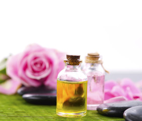 Pink roses with petals and massage oil with stone on mat