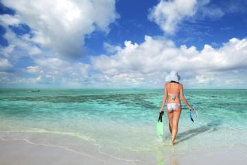 Slender woman in a bikini goes to swim in the sea