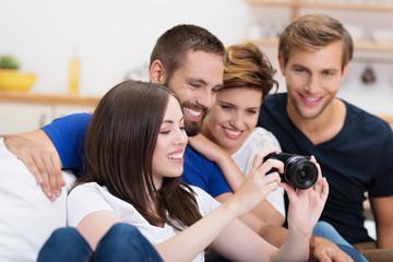 frau zeigt ihren freunden fotos auf der kamera