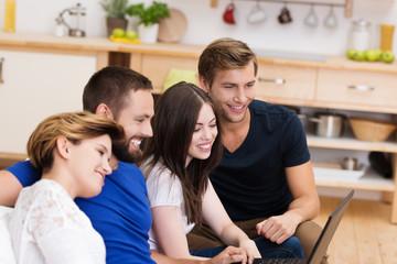 vier freunde schauen zu hause auf laptop