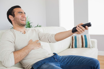 Handsome man bursting out laughing while watching tv