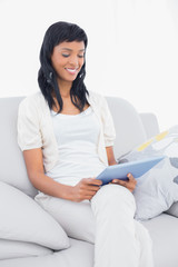 Thoughtful black haired woman in white clothes holding a tablet