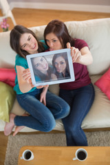 Two pretty friends on the couch taking a selfie with tablet pc