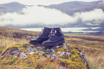 pair of old  black walking boots on a rock in the mountains