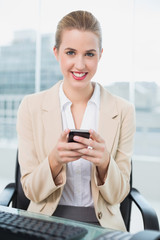 Cheerful attractive businesswoman text messaging