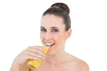 Woman drinking orange juice looking at camera