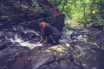 woman washing her hands in mountain stream