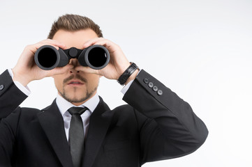 Businessmen with binoculars. Young businessmen looking through t