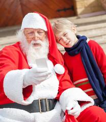 Santa Claus And Boy Taking Selfportrait Through Smartphone