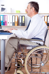 Man sitting in a wheelchair at the desk