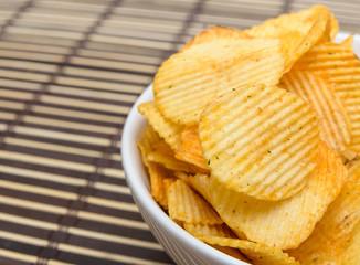 Potato chips in white bowl on bamboo mat