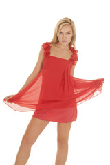 Woman red thin dress hold out skirt looking