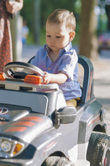 Portrait of Little Boy Managing to Drive a Scale Model